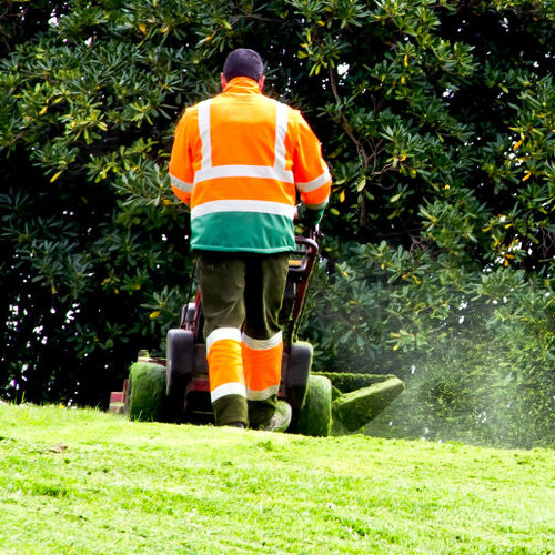 Worker mowing a large lawn.